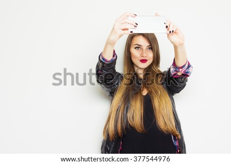 Beautiful modern blonde teenage girl in black leather jacket smiling, taking a selfie on smartphone. Cute young woman photographing herself using cellphone. Horizontal, copy space. - stock photo