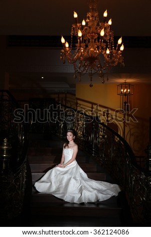 Beautiful modern bride in white wedding dress over black stairs  - stock photo