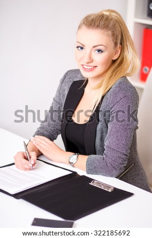 beautiful modern businesswoman in her office with a paper folder and tablet computer and mobile phone