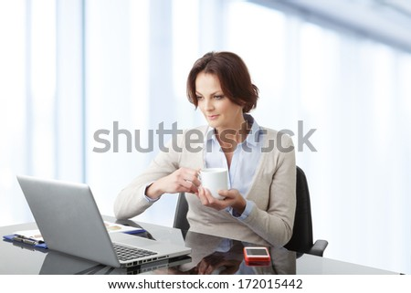 Beautiful modern businesswoman working on her laptop in office.