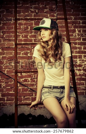 Beautiful modern girl near the brickwall in the rays of the evening sun. Youth style. Fashion shot. - stock photo