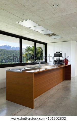 beautiful modern house in cement, interior, wooden kitchen island - stock photo