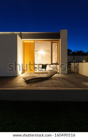 beautiful modern house in cement, view from the garden, night scene - stock photo