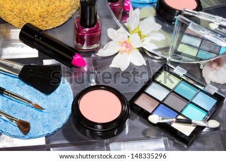 Beautiful modern make up with eye shadow in shades of blue, lipstick, blusher and brushes carefully displayed, high angle view - stock photo
