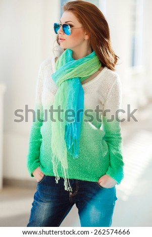 Beautiful modern woman with long red hair in a green-blue sweater and scarf outdoors. Woman with blue sunglasses. Smiling girl - stock photo