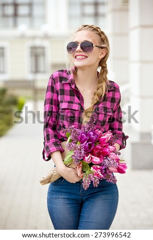 Beautiful modern young woman in springtime. Woman with bouquet of tulips and lilac. - stock photo