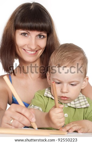 beautiful mom with her child drawing at table
