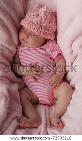 Beautiful month-old girl in a pink hat and a pink body.