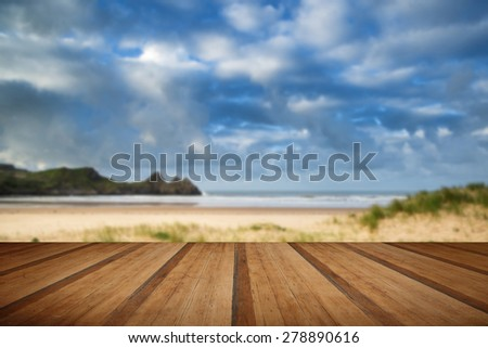 Beautiful morning landscape over sandy beach Three Cliffs Bay with wooden planks floor - stock photo