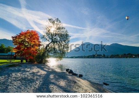 Beautiful morning on lake with mountains on background and baloon in the sky - stock photo