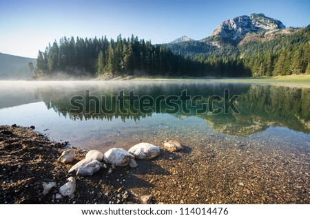 Beautiful morning on the mountain lake surrounded by forest - stock photo