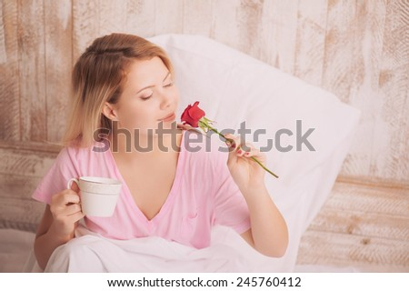 Beautiful morning. Top view portrait of young beauty drinking coffee in bed and holding a red rose while lying under the blanket - stock photo
