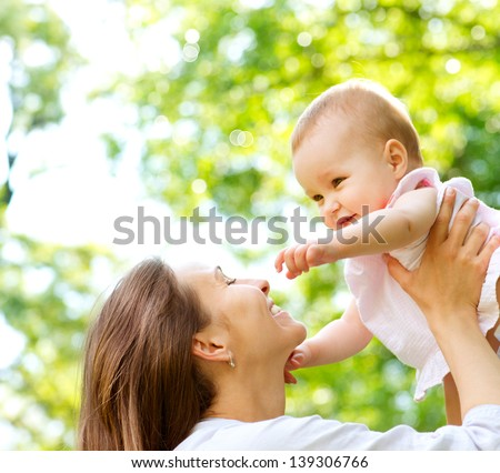 Beautiful Mother And Baby outdoors. Nature. Beauty Mum and her Child playing in Park together. Outdoor Portrait of happy family. Mom and Baby portrait - stock photo