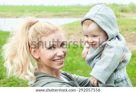 Beautiful Mother And Baby outdoors. Nature. Mum and her Child playing in Park together. Happy family.