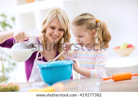 Beautiful mother and daughter baking pancakes