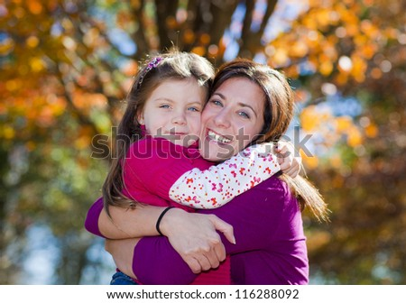 Beautiful mother and daughter hugging against fall background - stock photo