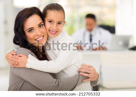 beautiful mother and daughter hugging in doctor's office - stock photo