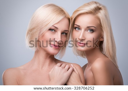 Beautiful mother and daughter in studio - stock photo