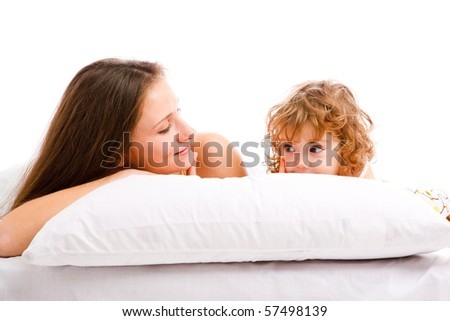 Beautiful mother and daughter lying on the pillow - stock photo