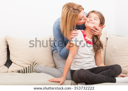 Beautiful mother and daughter on the couch or sofa as single mom concept