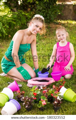 Beautiful mother and daughter planting flowers in the garden.
