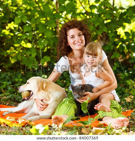 Beautiful mother and daughter relaxing in nature with pets - stock photo