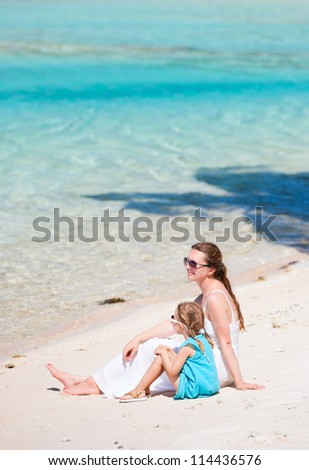 Beautiful mother and daughter sitting on a deserted tropical beach