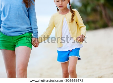 Beautiful mother and her adorable little daughter at beach - stock photo