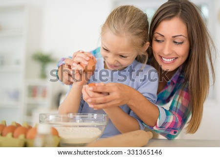 Beautiful mother and her daughter breaking eggs together in the domestic kitchen.