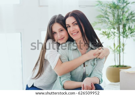Beautiful mother and her pretty daughter teenager smiling and posing at home