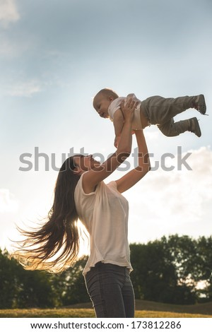 Beautiful mother and her son are having fun outdoors in sunshine - stock photo