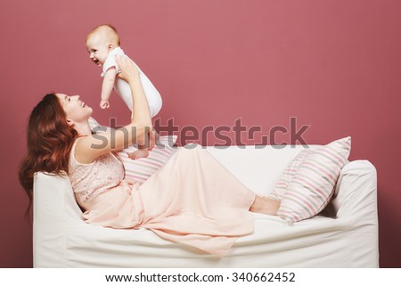 Beautiful mother and her son lying on the bed against the backdrop of a red wall - stock photo