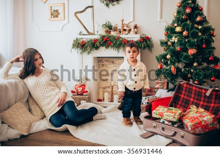 Beautiful mother and her son who sits on a toy horse - stock photo