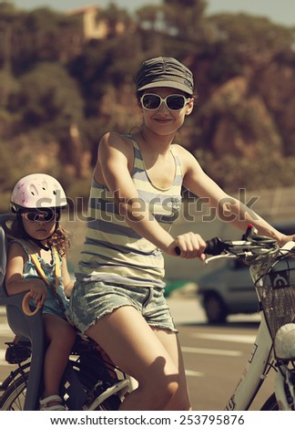Beautiful mother and kid riding on bicycle outdoors. Vintage portrait - stock photo