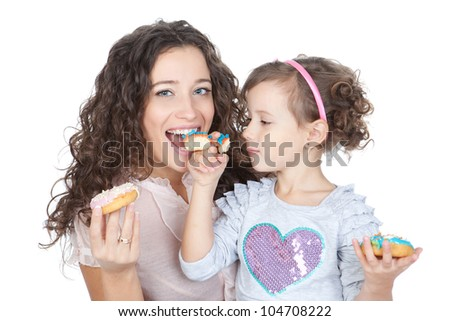 beautiful mother and little daughter eating colorful donuts over white background - stock photo