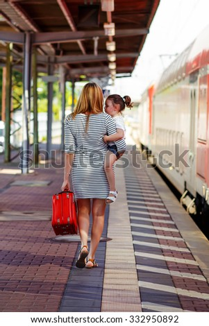 Beautiful mother and little daughter on a railway station. Kid and woman waiting for train and happy about a vacations. People, travel, family, lifestyle concept - stock photo