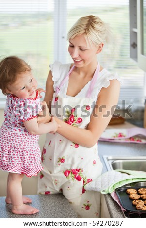 Beautiful mother baking with her daughter together in the kitchen - stock photo