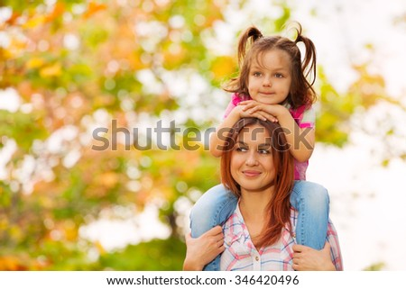 Beautiful mother carry little girl on shoulders