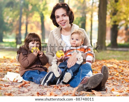 Beautiful mother embracing her little children in a autumn park - stock photo