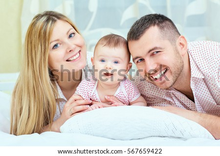 Beautiful mother, father and baby lying on the bed. Happy family