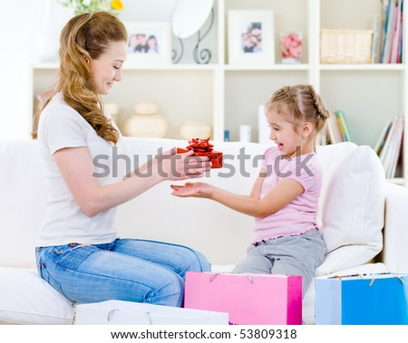 Beautiful mother giving a gift for her little pretty daughter  - at home - stock photo