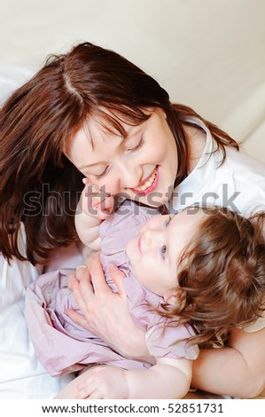 Beautiful mother hugs her 9-months baby-daughter