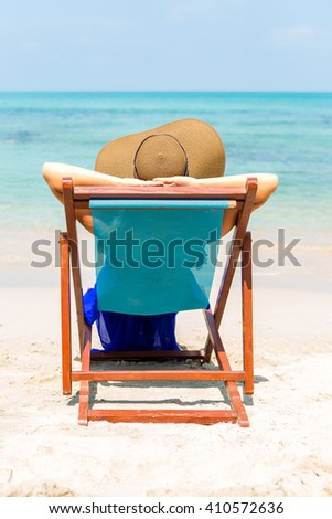 Beautiful mother in long blue dress and beach straw hat relaxing in a beach chair. Woman relaxing and look to the sea. Lady near coastline. Photo from back. Happy mothers day. - stock photo