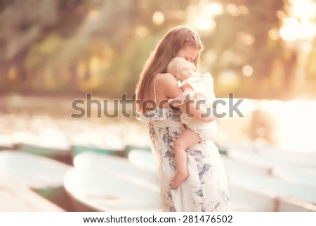 beautiful mother is standing on the pier and holding her little baby girl daughter on her hands and hugging her very gently at summer time on sunset - stock photo