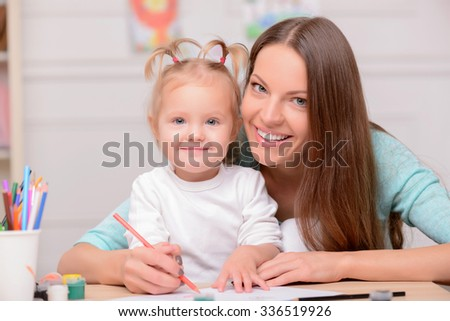 Beautiful mother is teaching her daughter to draw. They are sitting at the desk and smiling. The lady is embracing the girl - stock photo