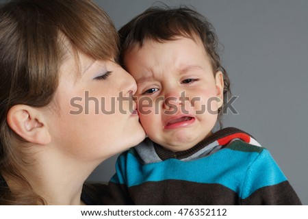 beautiful mother kissing her crying son