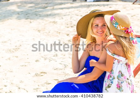 Beautiful mother lady in blue dress and beach straw hat with her pretty blonde cute daughter. Woman in a beach chair smile to little girl. Happy family on the beach. Happy mothers day. - stock photo