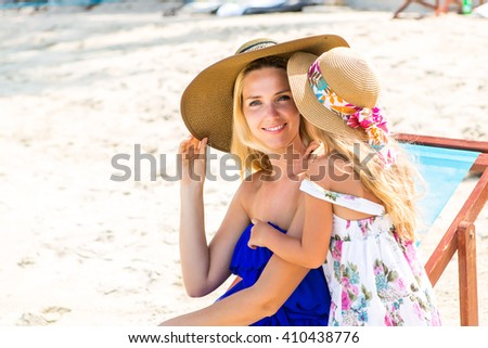 Beautiful mother lady with her pretty blonde cute daughter. Woman in a beach chair smile to the camera. Little girl say something to her ear. Happy family on the beach. Happy mothers day. - stock photo