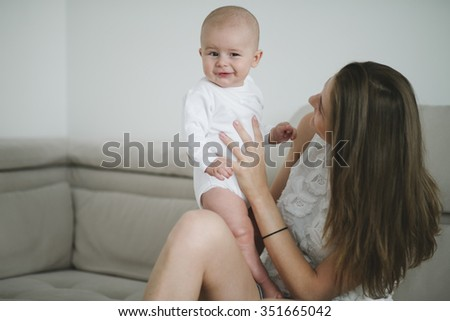 Beautiful mother portrait playing with her cute little boy on the sofa  - stock photo