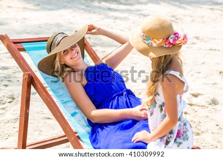 Beautiful mother relaxing in a beach chair. Her cute blonde daughter in dress and beach straw hat talk to she. Woman look to the camera and smile. Happy family on the shore. Happy mothers day. - stock photo